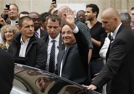 France's newly-elected President Francois Hollande waves as he leaves his campaign headquarters in Paris May 7, 2012, a day after the French presidential election. REUTERS/Benoit Tessier