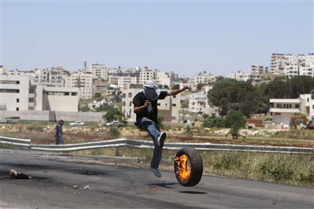 A Palestinian protester kicks a burning tyre towards Israeli troops during clashes outside Ofer prison near the West Bank city of Ramallah May 7, 2012. Clashes between Israeli troops and Palestinian stone-throwers broke out following a protest in solidarity with hunger striking Palestinian prisoners. The hunger strike against Israel's jail policies has swollen in weeks from a protest by a handful to a national movement with around 1,400 participants. REUTERS/Mohamad Torokman