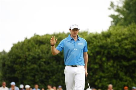 Rory McIlroy, of Northern Ireland, waves to the gallery after making a birdie putt on the second hole during the final round of the Wells Fargo Championship PGA golf tournament in Charlotte, North Carolina May 6, 2012. REUTERS/Chris Keane
