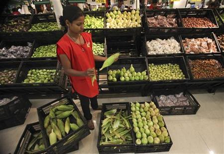 An employee arranges vegetables in the fresh foods section of a Reliance Fresh supermarket in Mumbai October 16, 2011. REUTERS/Danish Siddiqui/Files