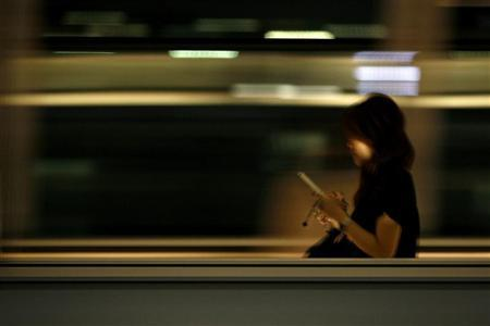A woman use her mobile phone as she walks on a moving walkway in Tokyo August 3, 2009. REUTERS/Stringer