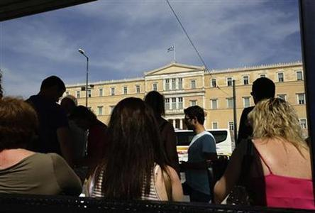 People stand in a bus shelter near the parliament in Athens May 7, 2012. REUTERS/Kevin Coombs