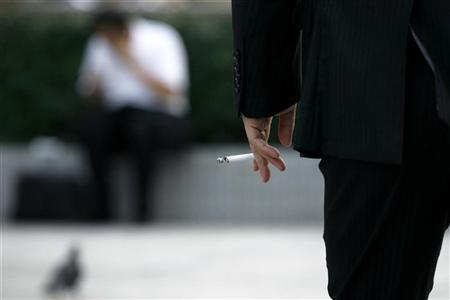 A man holds a cigarette in Tokyo August 3, 2009. REUTERS/Stringer
