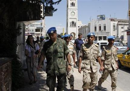 REFILE - CORRECTING CITY United Nations (U.N.) observers walk at al-Assi square during a field trip in Hama May 8, 2012. U.N.-Arab League mediator Kofi Annan and the U.N. peacekeeping chief gave a bleak assessment to the Security Council on the situation in Syria, where fighting continues and fears of full-scale civil war are increasing, U.N. diplomats said on Tuesday. REUTERS/Khaled al-Hariri