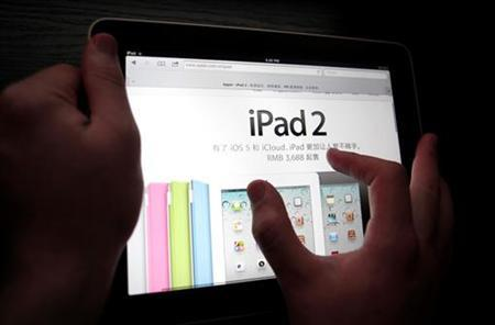 A man holds an an Apple Inc's iPad in this photo illustration March 3, 2012. REUTERS/Carlos Barria