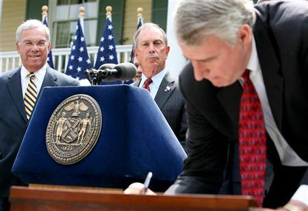 Boston Mayor Thomas Menino (L) and New York City Mayor Michael Bloomberg (C) watch as Milwaukee Mayor Tom Barrett signs a ''Statement of Principles'' intended to unite U.S. mayors in the fight against illegal guns during a ceremony at Gracie Mansion in New York, April 25, 2006. REUTERS/Jeff Zelevansky
