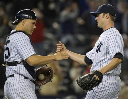 New York Yankees catcher Russell Martin congratulates relief pitcher David Robertson (R) after he pitched out of a bases-loaded jam and they beat the Tampa Bay Rays 5-3 in their MLB American League baseball game at Yankee Stadium in New York, May 8, 2012. REUTERS/Ray Stubblebine