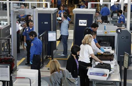 A man is screened with a backscatter x-ray machine as travellers go through a TSA security checkpoint in terminal 4 at LAX, Los Angeles International Airport, in Los Angeles May 2, 2011. REUTERS/Danny Moloshok