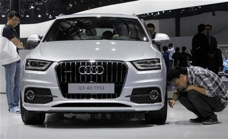 A visitor takes a photo of an Audi Q3 40 car with a Turbo Fuel Stratified Injection (TFSI) engine at Auto China 2012 in Beijing April 23, 2012. REUTERS/Jason Lee