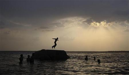 A boy prepares to jump off a rock into the waters of the Osman Sagar Lake near Hyderabad May 29, 2011. REUTERS/Krishnendu Halder