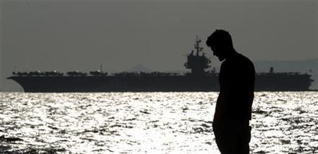 A man is silhouetted in front of the aircraft carrier USS Enterprise off the port of Piraeus, near Athens March 29, 2012. REUTERS/Yorgos Karahalis