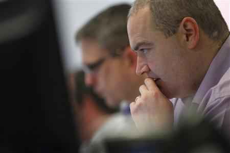 Traders from Interactive Investor look at their computer screens in their office in Glasgow, Scotland May 8, 2012. REUTERS/David Moir