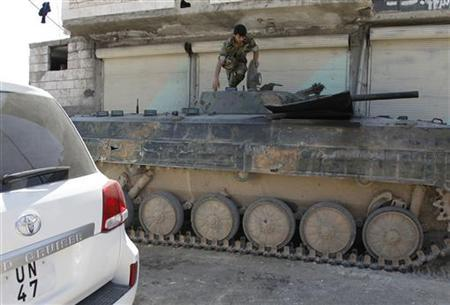A Syrian soldier climbs on a tank at a checkpoint at one of the entrances to Ariha city, during a field visit by U.N. observers to the Idlib areas, May 9, 2012. REUTERS/Khaled al- Hariri