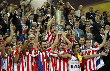 Atletico Madrid players hold up the trophy as they celebrate their Europa League final soccer match victory against Athletic Bilbao at the National Arena in Bucharest May 9, 2012. REUTERS/Ina Fassbender