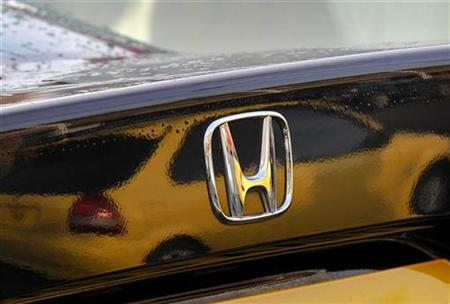 A Honda Civic car is seen reflected in the rear of another Honda at a showroom in west London January 30, 2009. REUTERS/Toby Melville