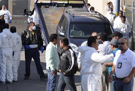 Police and forensic technicians stand near one of two cars containing the remains of ten people in the parking lot of the morgue in Guadalajara May 9, 2012. REUTERS/Alejandro Acosta