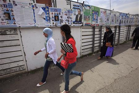 Women walk past electoral posters in Algiers May 9, 2012. REUTERS/Zohra Bensemra