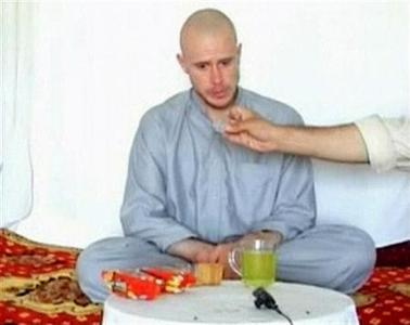 U.S. Army Private Bowe Bergdahl watches as one of his captors displays his identity tag to the camera at an unknown location in Afghanistan, July 19, 2009. REUTERS/via Reuters TV