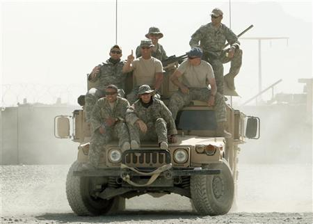 U.S. soldiers smile as they ride on top of a gun truck in Patrol Base Wilson in Zhari district. REUTERS/Goran Tomasevic