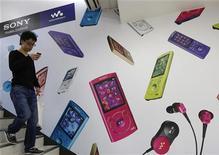 Мужчина спускается по лестнице перед рекламным плакатом плееров Sony Walkman в Токио, 10 мая 2012 года. Sony Corp получила рекордный чистый убыток в 456,7 миллиарда иен ($5,74 миллиарда) за минувший финансовый год в основном из-за проблем в телевизионном подразделении. REUTERS/Kim Kyung-Hoon