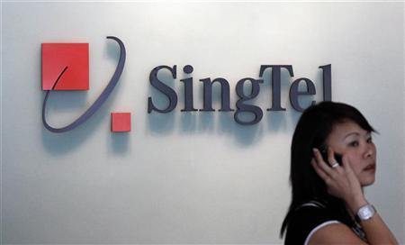 A woman speaks on a mobile phone in front of a SingTel logo at the company's headquarters in Singapore May 13, 2010. REUTERS/Vivek Prakash