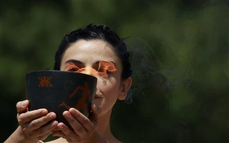 Greek actress Ino Menegaki, playing the role of High Priestess, carries a cauldron with the Olympic flame during the torch lighting ceremony of the London 2012 Olympic Games at the site of ancient Olympia in Greece May 10, 2012. REUTERS/John Kolesidis