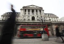 Люди проходят мимо Банка Англии в Лондоне, 14 февраля 2012 года. Банк Англии решил не вливать средства в проблемную экономику Великобритании, так как опасения по поводу высокой инфляции перевесили страхи о продолжительной рецессии и возобновлении угрозы со стороны долгового кризиса еврозоны. REUTERS/Olivia Harris