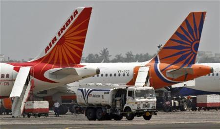 A fuel tanker moves past Air India passenger jets parked at an airport in Kolkata May 6, 2012. REUTERS/Rupak De Chowdhuri