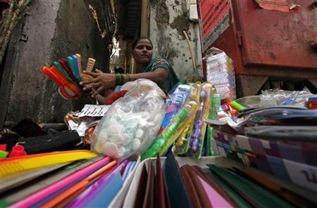 Tairabi Pathan, 40, who took a loan of rupees 10,000 from a micro finance company to start her own business, arranges her goods for sale at the side of a road in a slum area in Mumbai October 26, 2010. REUTERS/Danish Siddiqui/Files