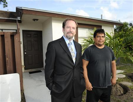 Roman Pino (R) stands with his attorney Thomas Ice in front of his home that was deeded back to him by the bank after facing foreclosure in Greenacres, Florida, May 3, 2012. REUTERS/Doug Murray