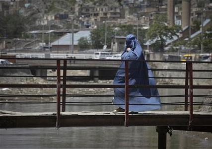 An Afghan woman clad in burqa crosses pedestrian bridge over a river at the old part of Kabul, May 10, 2012. REUTERS/Danish Siddiqui