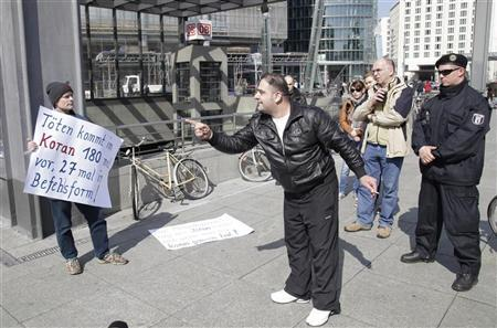 A man argues with a protester as members of ultra-conservative Salafist Muslim group hand out copies of German-language versions of the Koran at the Potsdamer Platz square in downtown Berlin, April 14, 2012. REUTERS/Tobias Schwarz
