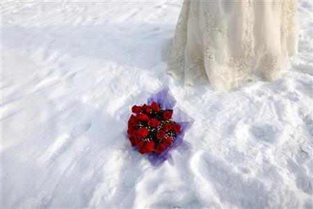 A bouquet is seen in the snow as a bride poses for a photograph after a group wedding ceremony in Harbin, China, January 6, 2010. REUTERS/Aly Song