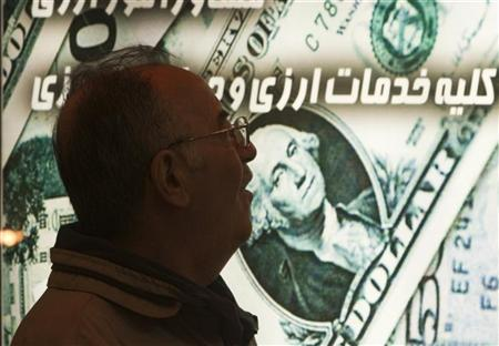 EDITORS' NOTE: Reuters and other foreign media are subject to Iranian restrictions on leaving the office to report, film or take pictures in Tehran. An Iranian man walks past a currency exchange shop in northern Tehran January 3, 2012. REUTERS/Morteza Nikoubazl