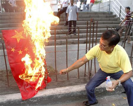 An activist burns a flag of China during a protest to demand that the Chinese government pull out from the Scarborough Shoal during a rally in front of the Chinese consular office in Makati's financial district of Manila May 8, 2012. REUTERS/Cheryl Ravelo