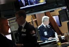 Трейдеры следят за ходом торгов на бирже в Нью-Йорке, 10 мая 2012 года. Индексы Dow и S&P 500 завершили торги четверга небольшим ростом, но разочаровывающий прогноз от технического гиганта Cisco Systems и бдительность в отношении Европы ограничили подъем. REUTERS/Brendan McDermid