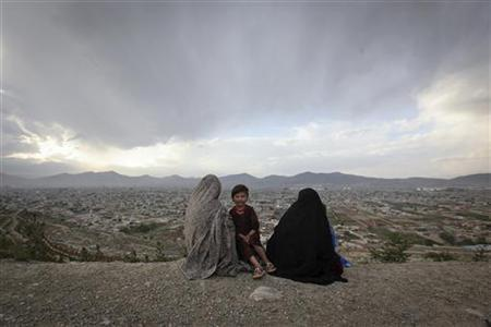 An Afghan family sits on a hill overlooking part of the Kabul city May 7, 2012. REUTERS/Danish Siddiqui