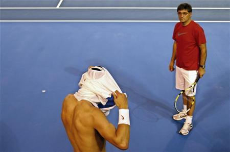 Rafael Nadal of Spain changes his shirt as his coach and uncle Toni Nadal watches during a training session at Melbourne Park January 13, 2011, ahead of the Australian Open tennis tournament, which begins on Monday. REUTERS/Petar Kujundzic