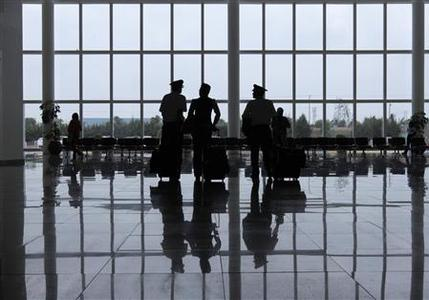 Flight personnel stand inside the airport in Puebla May 10, 2012. REUTERS-Imelda Medina