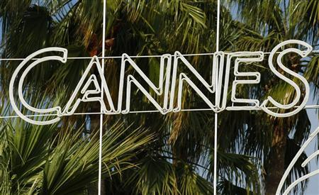 A palm tree is seen behind a Cannes logo May 10, 2010. The Cannes Film Festival, the world's biggest, runs from May 12 to 23. REUTERS/Yves Herman