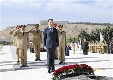 Syria's President Bashar al-Assad (C) visits to place flowers on the tomb of the Unknown Soldier on the occasion of Martyrs' Day, in Damascus May 6, 2012, in this handout released by Syria's national news agency SANA. REUTERS/SANA/Handout