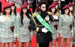 """Ator Sacha Baron Cohen, interpretando o Admirável General Aladeen, aponta arma enquanto posa com modelos na estreia mundial de """"O Ditador"""" no Royal Festival Hall, em Londres. 10/05/2012 REUTERS/Paul Hackett"""