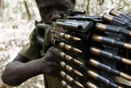 A Ugandan soldier tracking down Lord's Resistance Army (LRA) fugitive leaders takes position behind a machine gun at a forest bordering Central African Republic (CAR), South Sudan and Democratic Republic of Congo, near river Chinko April 18, 2012. REUTERS/Stringer