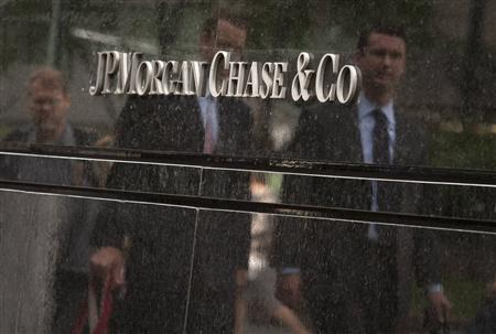 Commuters are reflected in stone as they walk past the JP Morgan headquarters in New York on May 11, 2012. REUTERS/Eduardo Munoz
