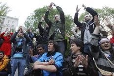 Активисты из лагеря противников российского президента Владимира Путина на Чистых прудах в Москве приветствуют колонну ОМОНа 9 мая 2012 года. Протестующие против возвращения Путина в Кремль шестой день не уходят с московских улиц. Власти приостановили полицейскую операцию против гуляющих без разрешения, но обещают неминуемую зачистку и миллионные штрафы недовольным, за которых вступились Запад и лояльные Кремлю общественные деятели. REUTERS/Denis Sinyakov