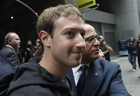 Facebook Inc. CEO Mark Zuckerberg is escorted by security guards as he departs New York City's Sheraton Hotel May 7, 2012. REUTERS/Eduardo Munoz
