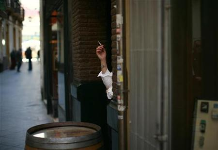 A woman smokes a cigarette in the Andalusian capital of Seville February 16, 2012. REUTERS/Marcelo del Pozo