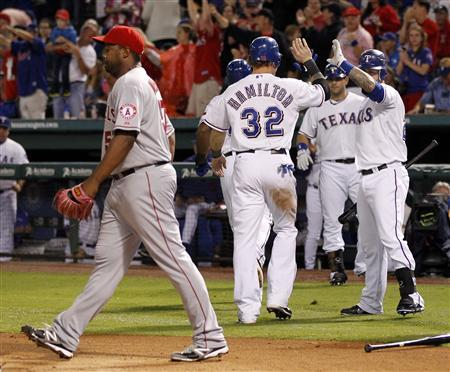Texas Rangers' Josh Hamilton is congratulated by teammate Mike Napoli (R) after hitting a home run against Los Angeles Angels pitcher Jerome Williams (L) in the first inning of their MLB American League baseball game in Arlington, Texas May 11, 2012. REUTERS/Mike Stone