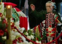 """Футбольный болельщик на похоронах форварда """"Бенфики"""" Миклоша Фехера на стадионе """"Да Луш"""" в Лиссабоне 27 января 2004 года. Преданные болельщики лиссабонской """"Бенфики"""", одного из сильнейших футбольных клубов Португалии, могут отныне не волноваться за свои похороны: в загробную жизнь их проводят со скидкой, что стало возможным после соглашения между их любимым клубом и крупнейшим в стране бюро ритуальных услуг. REUTERS/Nacho Doce"""