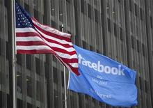 Флаг с объявлением об IPO Facebook рядом с флагом США возле офиса J.P. Morgan в Нью-Йорке 4 мая 2012 года. Сооснователь Facebook Inc Эдуардо Саверин отказался от американского гражданства за считанные дни до ожидаемого первичного размещения акций интернет-гиганта. REUTERS/Lee Celano